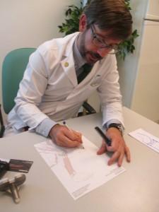 Doctor Alonso Bau, dibujando una rodilla con artrosis y explicando colocación de prótesis de rodilla